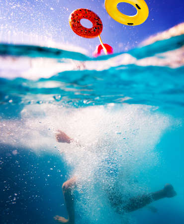 Split photo of a child dive in the water of swim pool with bubbles splashes and flying inflatable doughnut Archivio Fotografico