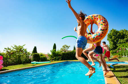 Happy many teenage kids with inflatable buoys dive into swimming pool jumping together view from side