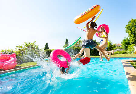 Group of happy teenage kids with inflatable toys jump and splash into water pool jumping together view from side Archivio Fotografico