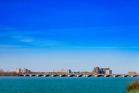 MacArthur bridge over Detroit river and city view on sunny day from sunset point of Belle Isle