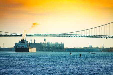 Ambassador Bridge view from Windsor Ontario Canada to Detroit, MI USA and freight boat passing by with steam over sky Фото со стока