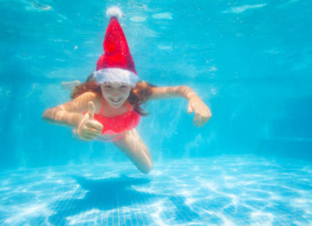 Happy girl with thumb up gesture dive and swim underwater wearing Santa Claus hat in the pool