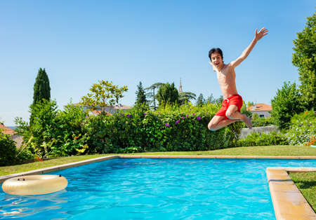 Teenage boy jump in mid air into the swimming pool view from side scream and smile