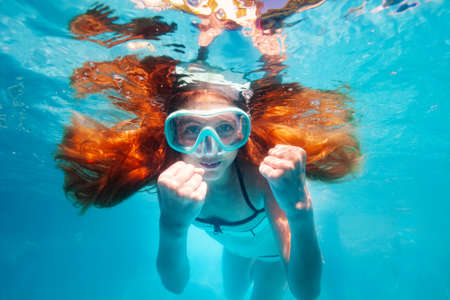Beautiful underwater portrait of the smiling little girl with long hairs wearing scuba mask show hands gesture