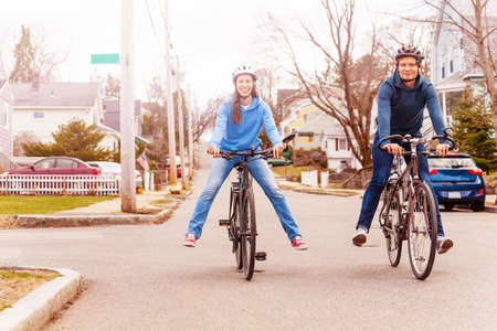 Husbands and wife ride a bicycle fun lifting legs smile on urban American street Reklamní fotografie