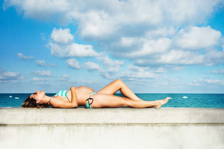 Profile photo of a pregnant woman lay on the border of the pool holding belly, view over sky