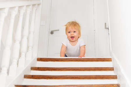 Little toddler boy looks down scared of staircase