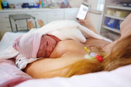 Mother feeding newborn baby with phone