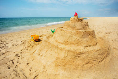 Side view of sand castle and toys on the sea beach