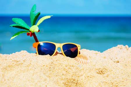 Kids sunglasses and toy palm in sand on sea beach Zdjęcie Seryjne