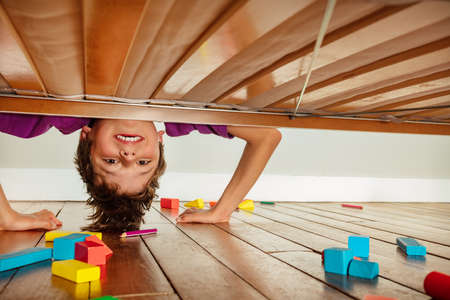 Boy look down under the bed make funny face Stock Photo