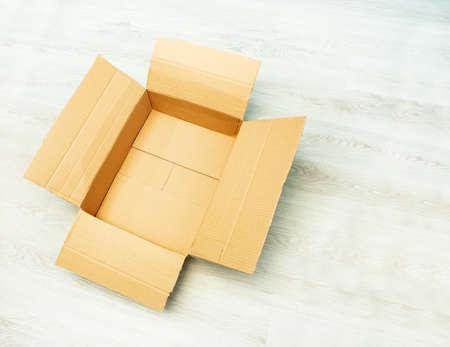 Empty open cardboard box on the parquet floor Zdjęcie Seryjne
