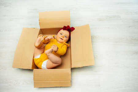 Baby girl with red bow in open cardboard box