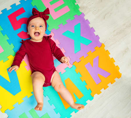 Cute little baby girl with red bow on ABC carpet Zdjęcie Seryjne