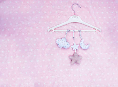Mobile baby toys hanging on a pink dotted blanket