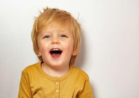 Close happy blond little boy portrait laughing