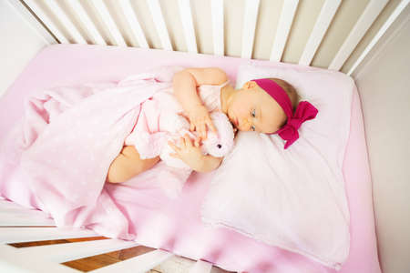 baby lay in crib bed with calm expression hug toy