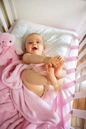 Baby girl lay in pink bed touching legs laughing Zdjęcie Seryjne
