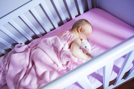 View from side of little baby girl sleep with toy