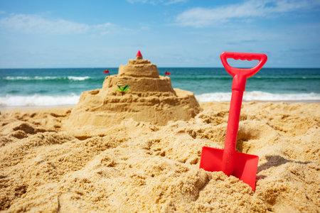 Toy scoop and sand castle build on the sea beach Zdjęcie Seryjne