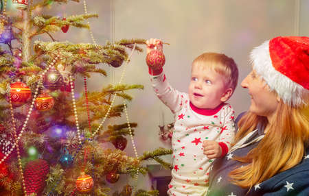 Mother and little toddler decorate Christmas tree Zdjęcie Seryjne