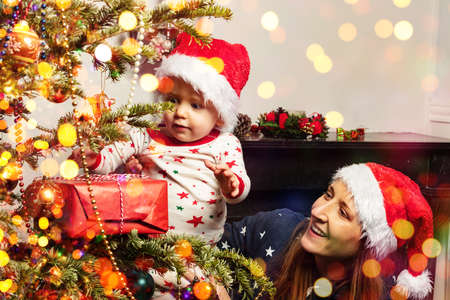 Toddler find Christmas present with mother near