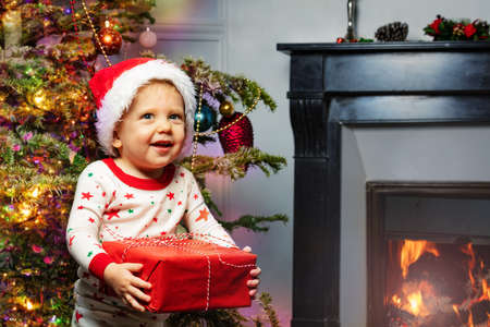 Toddler and present in Santa hat by Christmas tree Zdjęcie Seryjne