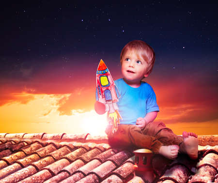 Baby boy play with paper rocket sitting on roof