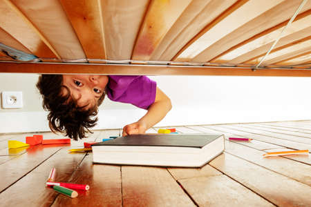 Boy finds book under the bed leaning down
