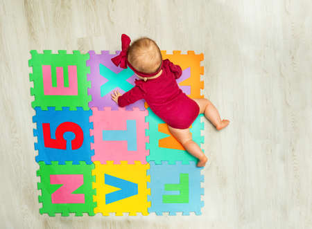 Happy baby girl creep on the carpet with letters Zdjęcie Seryjne