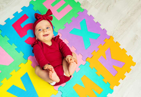 Happy baby girl lay on the carpet with letters