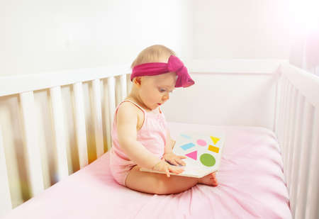 Baby sit in crib bed look at the book with shapes Zdjęcie Seryjne