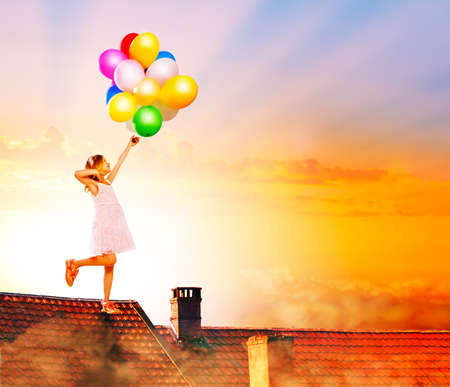 Little girl jump with balloons on the house roof