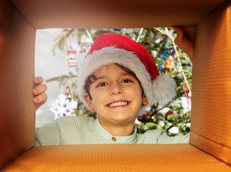 Child looks in present box wearing Santa hat Zdjęcie Seryjne