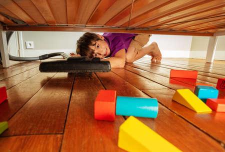 Boy vacuum clean under the bed full of toy blocks Zdjęcie Seryjne