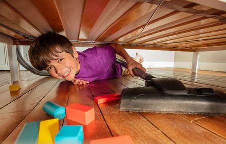 Boy under the bed clean floor with vacuum cleaner Zdjęcie Seryjne
