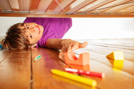 Boy stretch to reach color toy block under the bed
