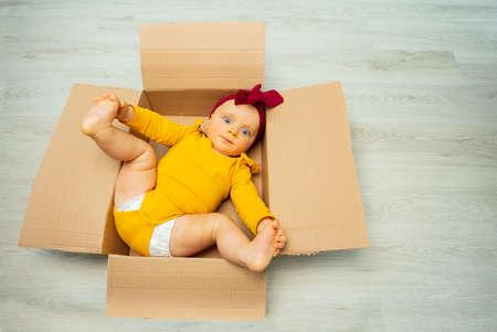 Baby girl in open cardboard box on the floor Zdjęcie Seryjne