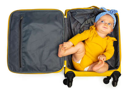 Little baby toddler girl in the empty travel case