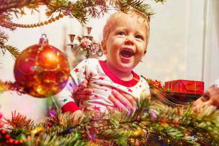 Laughing toddler cute boy by Christmas tree Zdjęcie Seryjne