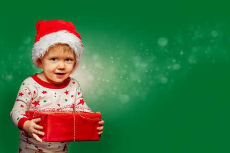 Little boy hold present box wearing Santa hat