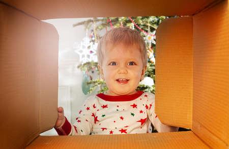 Happy toddler smiling boy looks inside present box