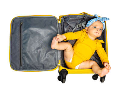 Baby girl lay in empty travel hand luggage suit