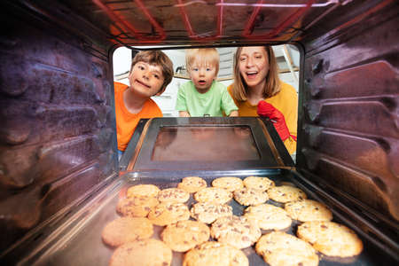 Mother and boys check fresh baked biscuits in oven