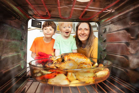 Mother and two boys take roasted chicken from oven