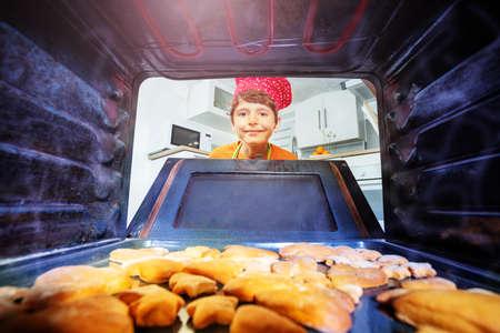 Happy laughing boy open oven door to take cookies