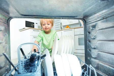 Little blond toddler take dishes from dishwasher Zdjęcie Seryjne