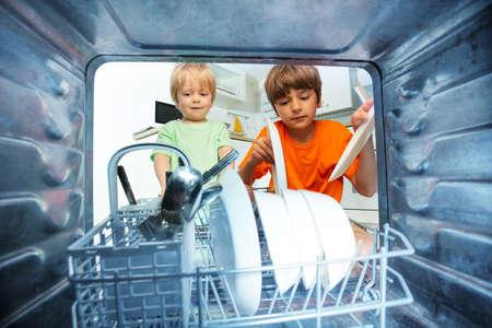Two boys together take dishes form the dishwasher Zdjęcie Seryjne