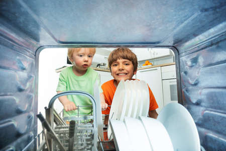Two boys unload plates from dishwasher inside view