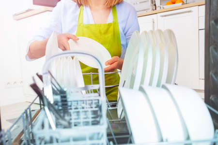 Closeup, woman take dishes out of the dishwasher